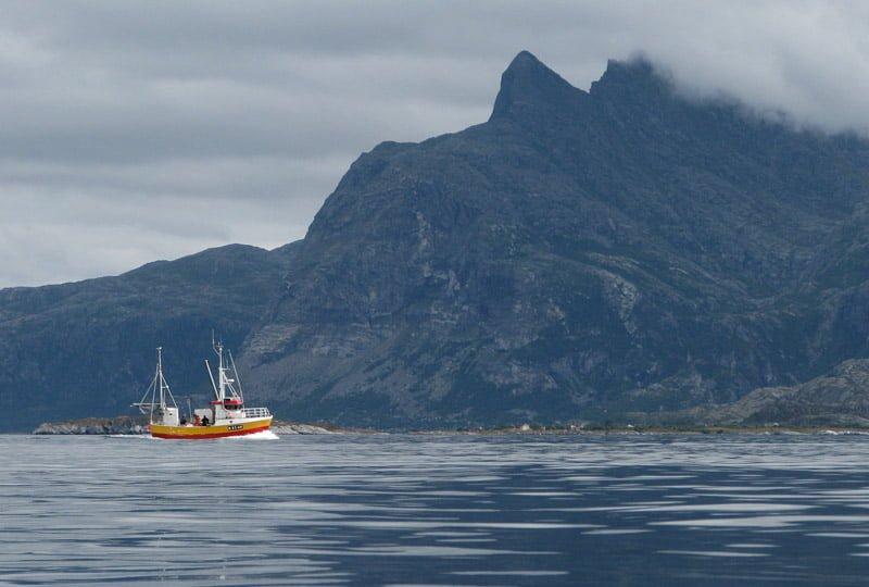 Fiskebåt med Dönnamannen i bakgrunden