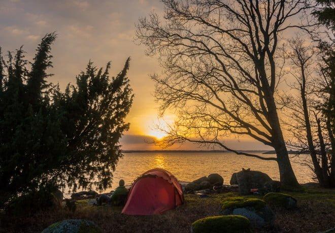 Skönt morgonljus över tält och vy mot Hasslö