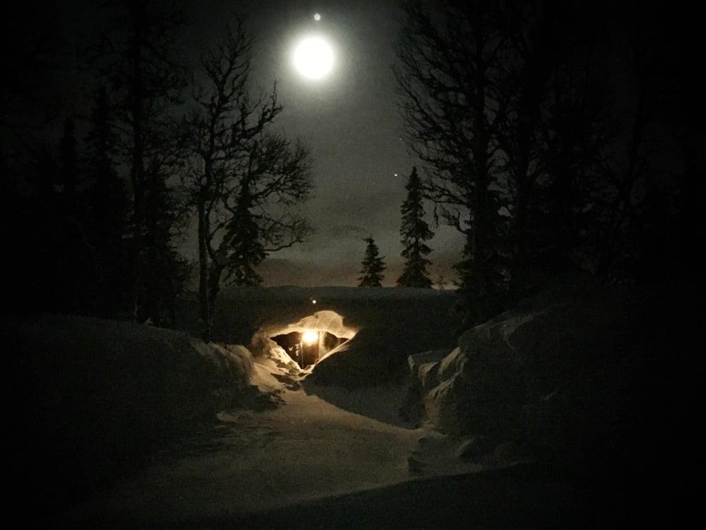 Fullmåne och insnöad stuga